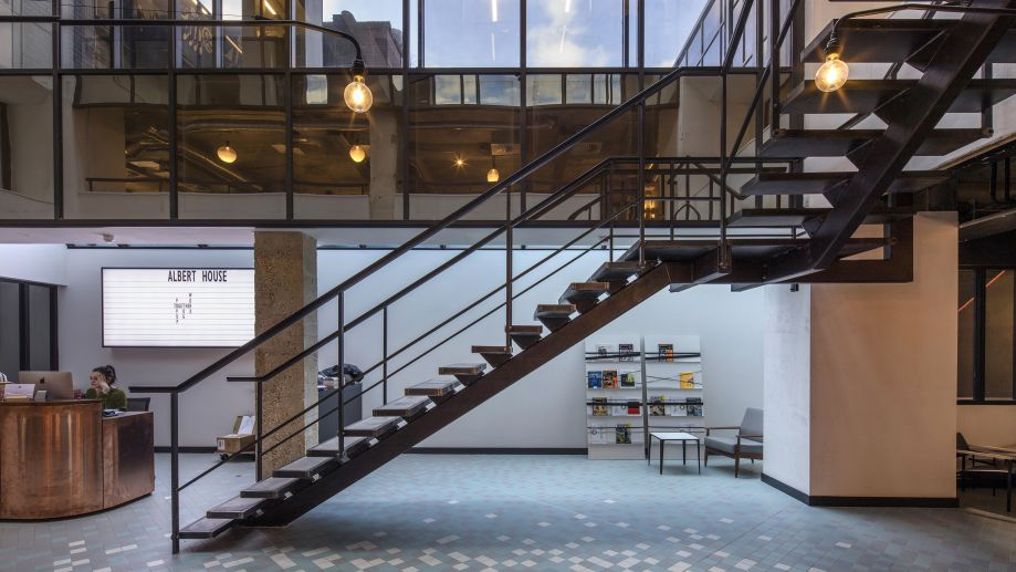 Open, industrial-style reception area at Albert House with a central staircase, tiled floor and large windows.