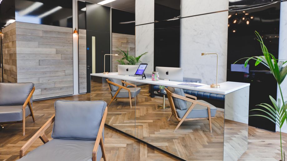 Reception at the Gridiron Building with parquet wooden flooring, mirrored reception desk and stylish grey seating.