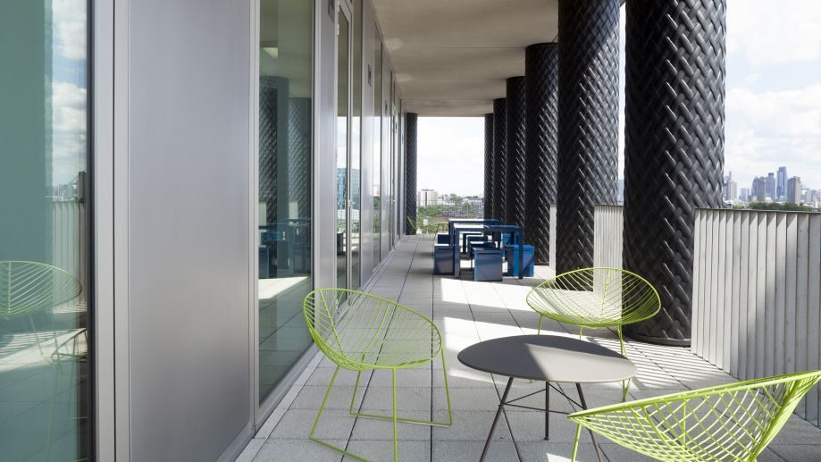 Contemporary roof terrace at the Gridiron building with large pillars, neon wire seating, low tables and views across London.