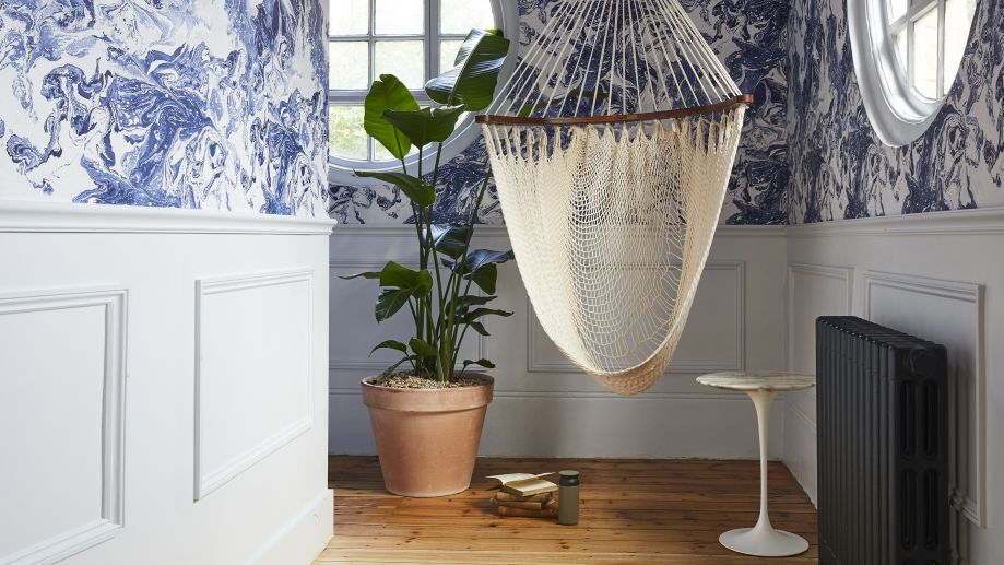 Melcombe Place library corner with blue patterned wallpaper, a hanging chair and leafy plant.