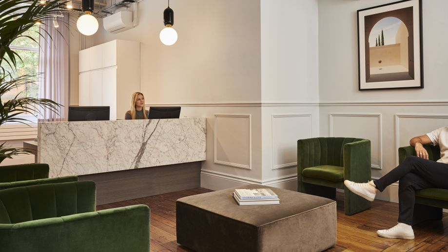 Melcombe Place reception with marbled front desk, white panelled walls and velvet seating.