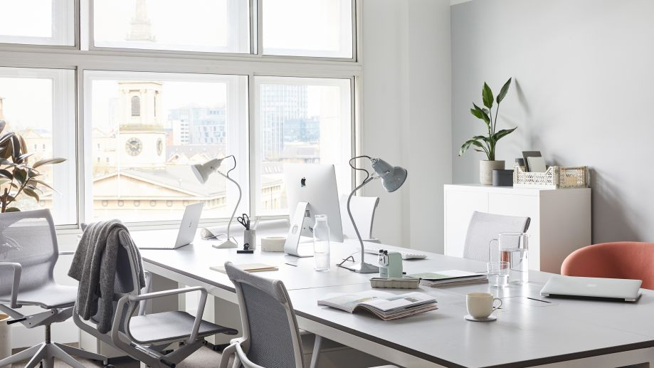 Light-filled office space at Scott House with a long desk, office chairs and windows with views of London.