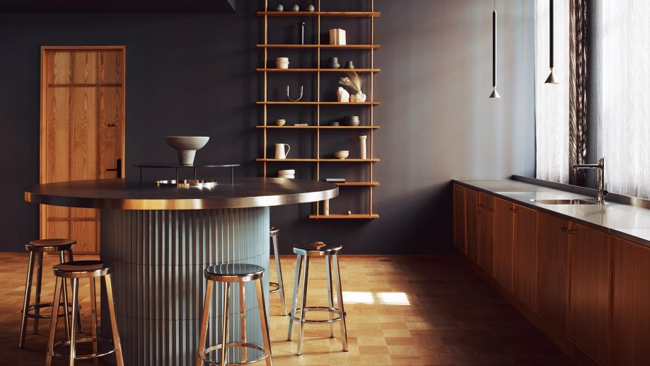Communal kitchen at Summit House with a round, dark panelled breakfast bar with metal stools and wooden shelving.