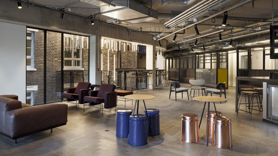 Stanley Building's industrial-style club room with exposed brickwork and a range of relaxed seating and tables.