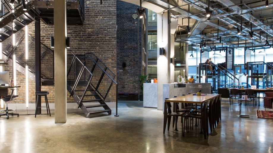 Coworking lounge at The Stanley Building with exposed brickwork, metal staircase, a café and shared working desks.