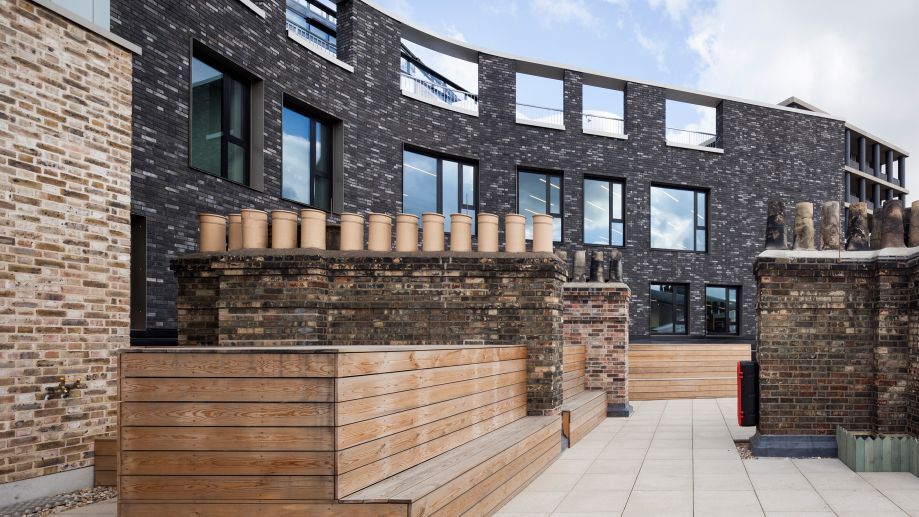 Roof terrace at The Stanley Building in King's Cross with decked seating and original chimney pots.